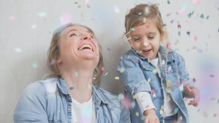 Mama und Tochter spielen mit Konfetti