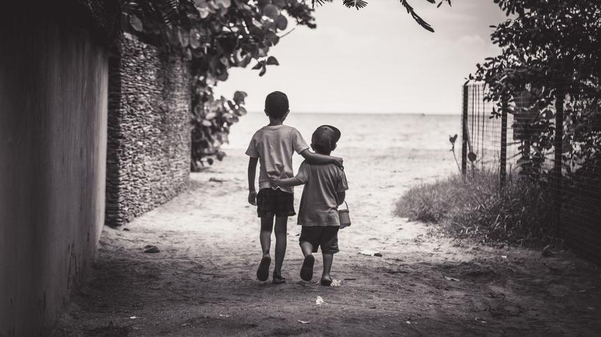 Zwei Jungen gehen nebeneinander Arm in Arm, schwarz-weiß