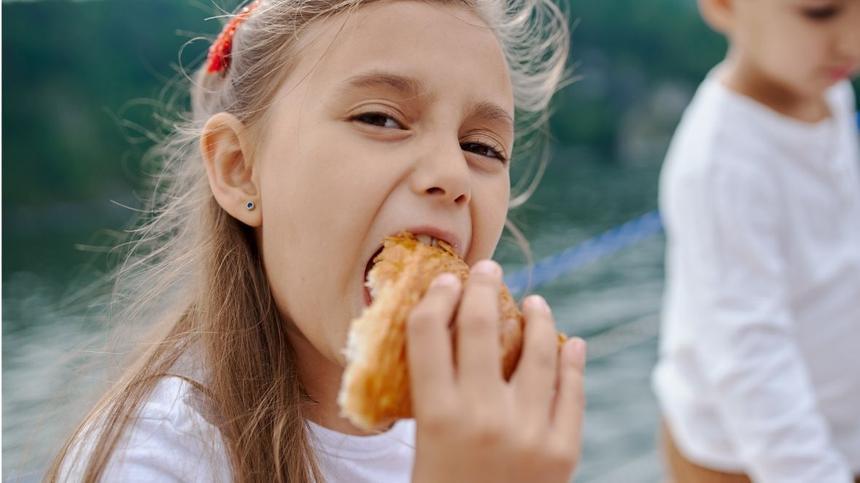 Mädchen beißt in Croissant