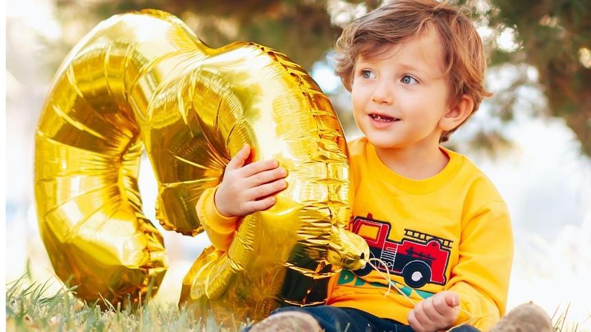 Junge hält Zahlenluftballon 3 hoch