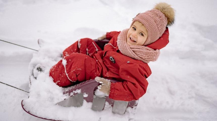 Kleines Kind sitzt auf Schlitten im Schnee