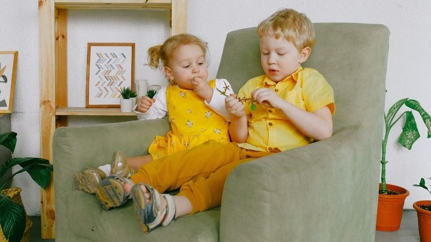 Bruder und Schwester sitzen gemeinsam auf Sessel und Essen