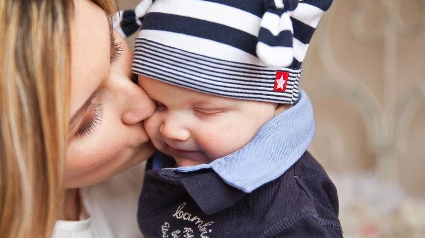 Frau küsst kleines Baby auf die Wange