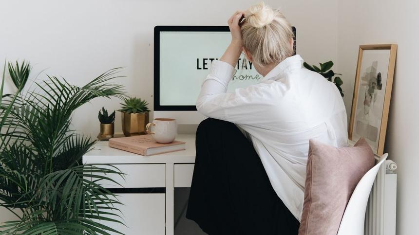 Frau sitzt an Schreibtisch und stützt Ellenbogen ab