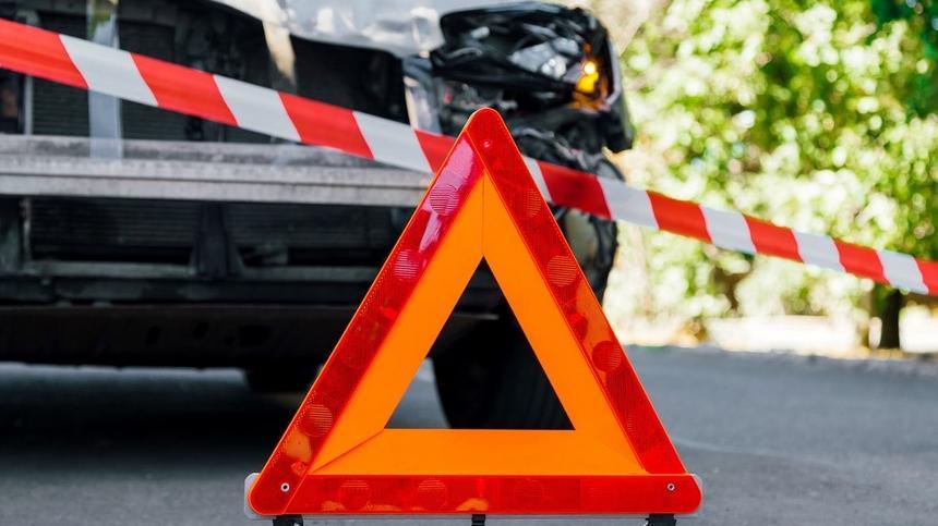 rot-orangenes Warndreieck vor Unfallauto und Absperrband
