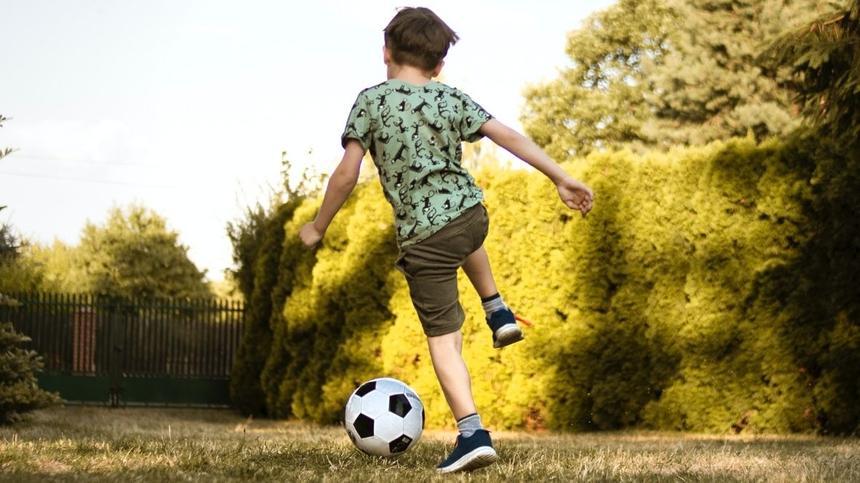 Junge spielt mit Fußball auf einer Wiese