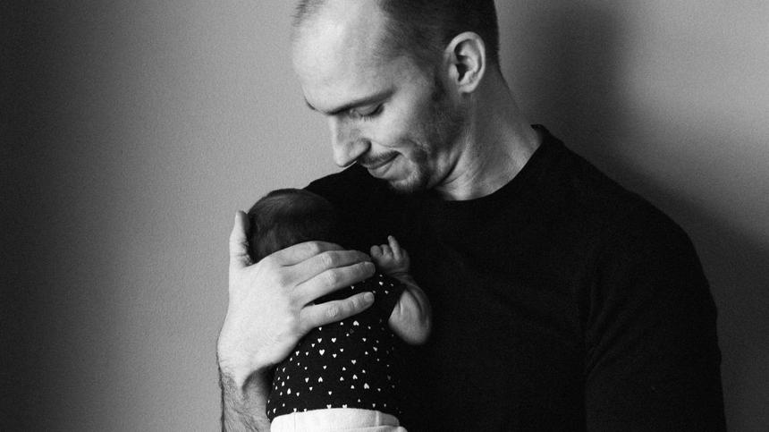 Schwarz-weiß Bild von Vater mit Baby aufm Arm