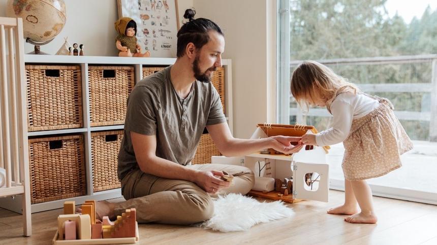 Vater spielt mit kleinem Mädchen und Puppenhaus