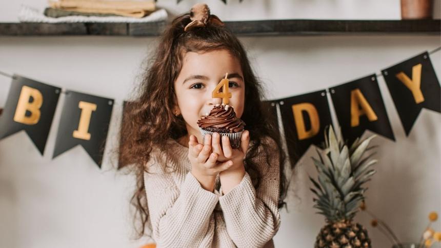 Mädchen hält dekorierten Muffin mit Kerze in Zahlenform Vier hoch