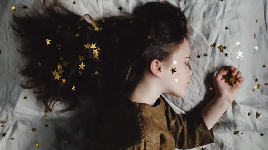 Mädchen liegt auf Bett mit Sternen im Haar und der Hand