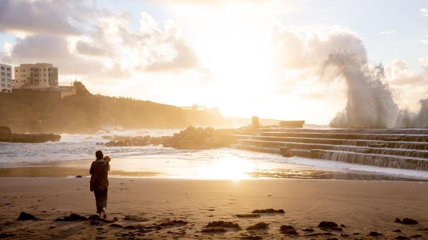 Frau mit Baby am Strand