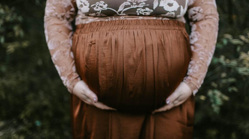 Frau zeigt Babybauch in die Kamera