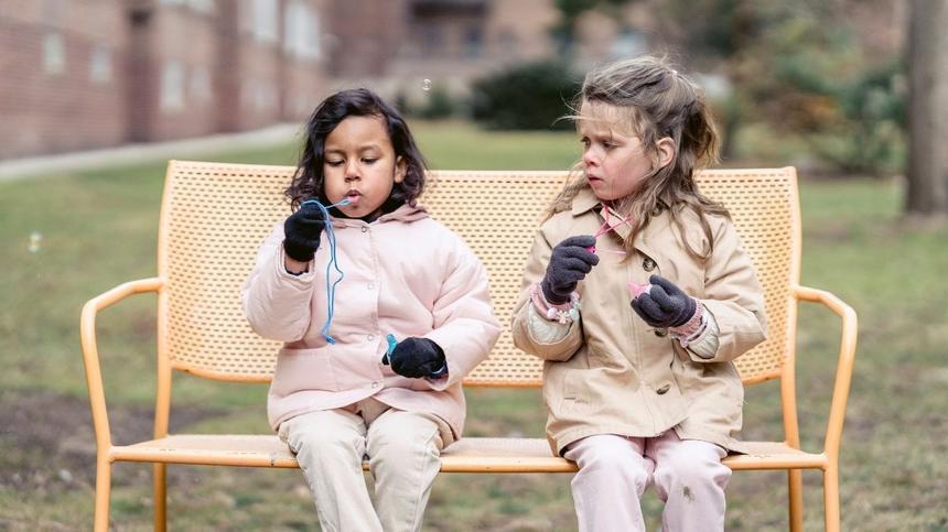 Zwei Kinder sitzen auf einer Bank und pusten Seifenblasen