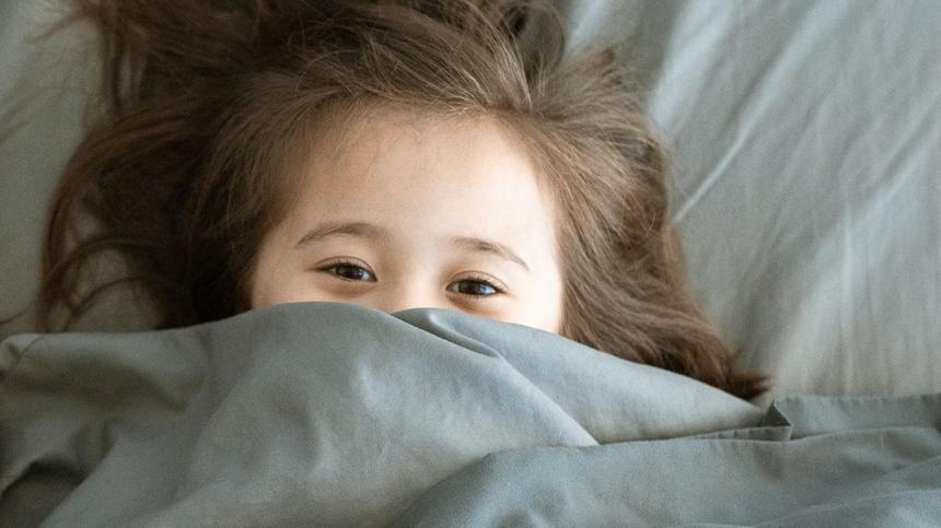 Mädchen liegt im Bett und kann nicht einschlafen