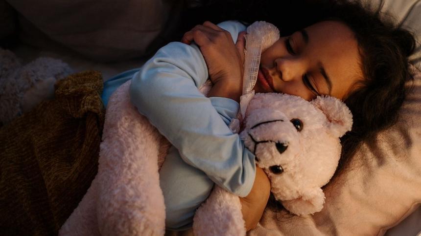 Kind hält Kuscheltier zum Einschlafen fest im Arm