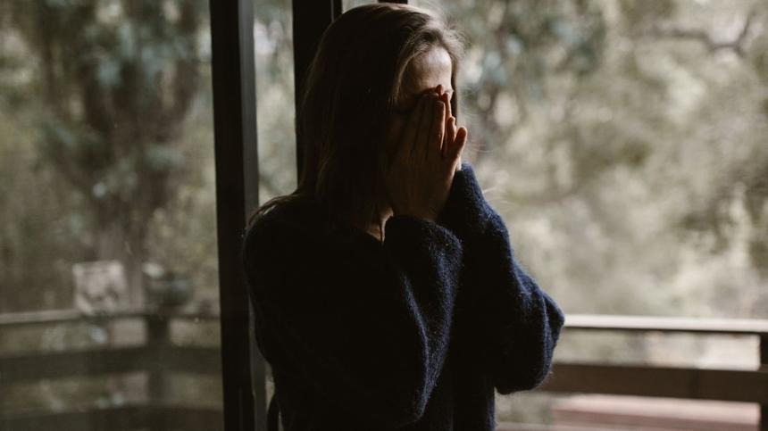 Verzweifelte Mutter am Fenster