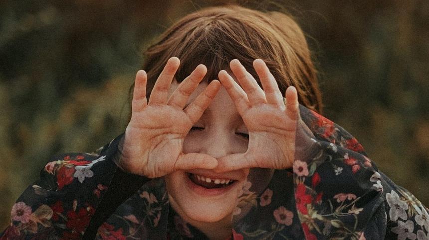Mädchen macht Kindergarten-Fingerspiele und hält sich die Hände vor die Augen.