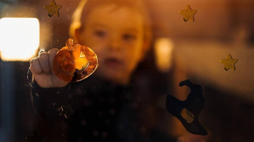 Kind klebt Herbst-Fensterbild an die Scheibe und spielt damit