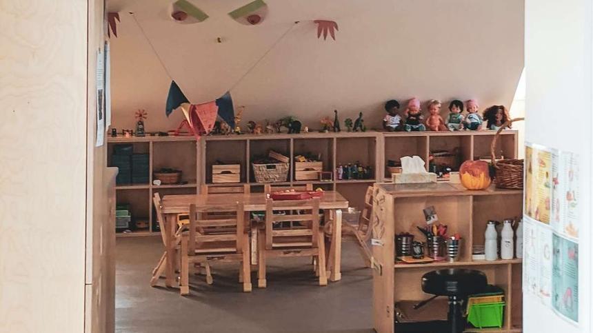 Kita-Betreuungsraum mit Stühlen und Tisch