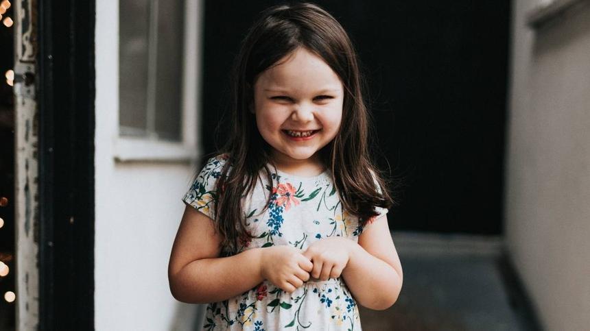 Mädchen lacht und hält die Hände zusammen