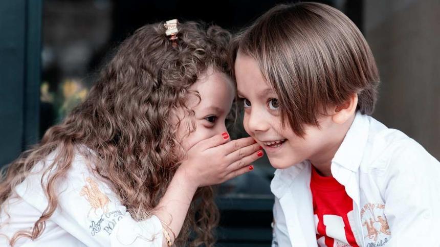 Kind flüstert einem anderen etwas zu und beide lachen