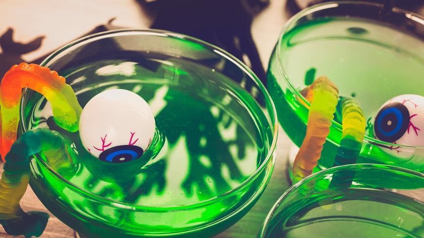 In einer grünen Halloween-Bowle für Kinder schwimmen Augen und Gummi-Würmer
