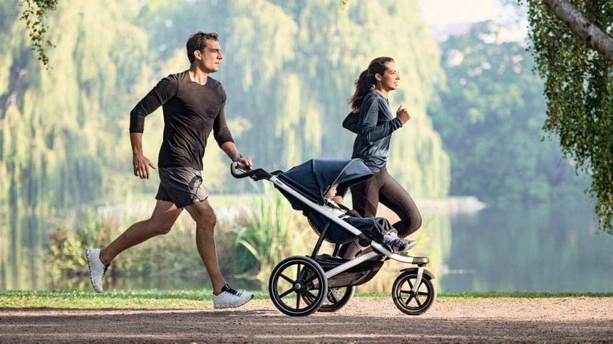 Eltern joggen mit dem Thule Urban Glide 2 durch den Park