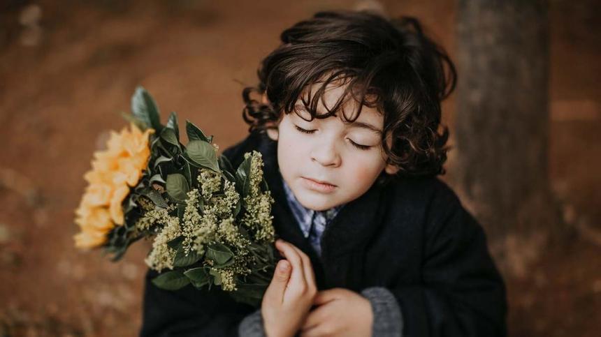 Junge mit langen Haaren hält einen Strauss Rosen
