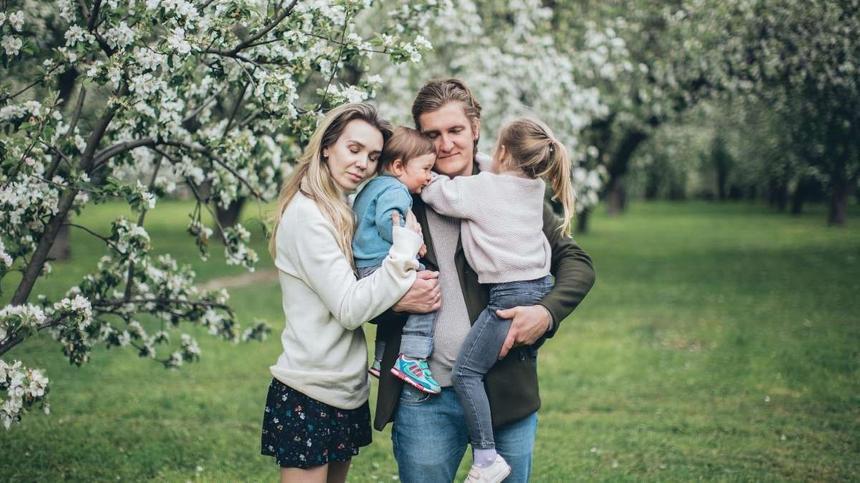 Familie mit zwei Kindern vor einem Kirschbaum im Garten
